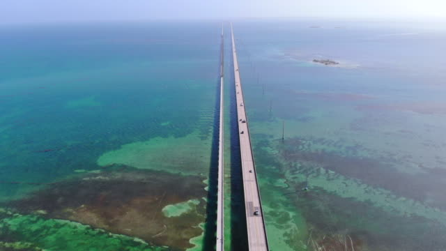 vídeos de stock, filmes e b-roll de drone view of the overseas highway in florida keys with turquoise color and infinite road. - perspectiva espacial