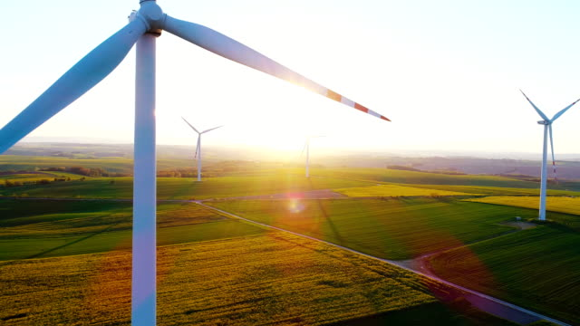 Drone view of windmill turbine at dawn.