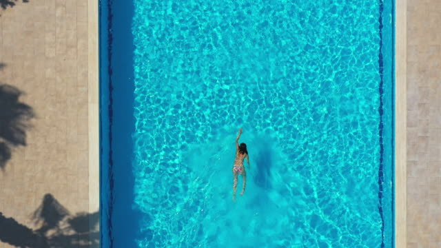 drone view of woman swimming in the pool - jumping stock videos & royalty-free footage