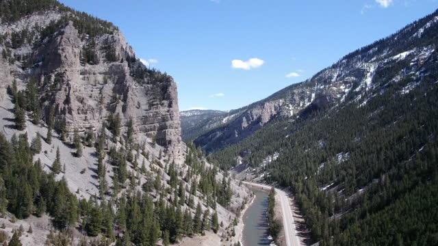 2車線の高速道路沿いの山岳地帯のワイオミング川のドローンビュー - グランドティトン国立公園点の映像素材/bロール