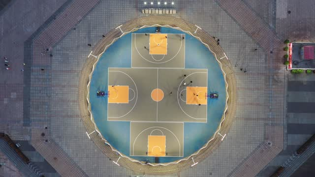 drone view of young adult men playing basketball together on public sports court at dusk. qingdao city, shandong province, china - abstract stock videos & royalty-free footage