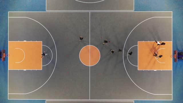 vídeos y material grabado en eventos de stock de drone view of young adult men playing basketball together on public sports court at dusk. qingdao city, shandong province, china - matematicas