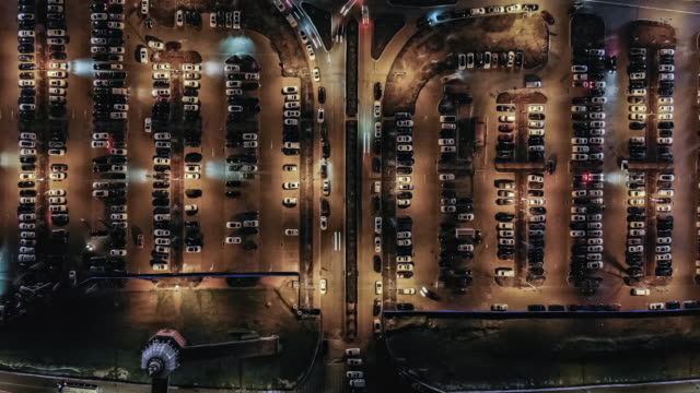 t/l pan drone view over outdoor parking lots at night - parking stock videos & royalty-free footage
