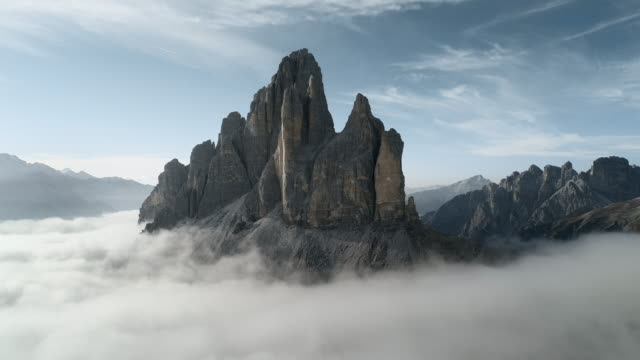 drone view showing clouds swirling at the foot of a mountain peak, tre cime di lavaredo, dolomites, italy - tre cimo di lavaredo stock videos & royalty-free footage