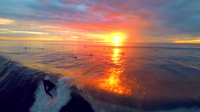 Drone view Surfer rides waves during sunset close