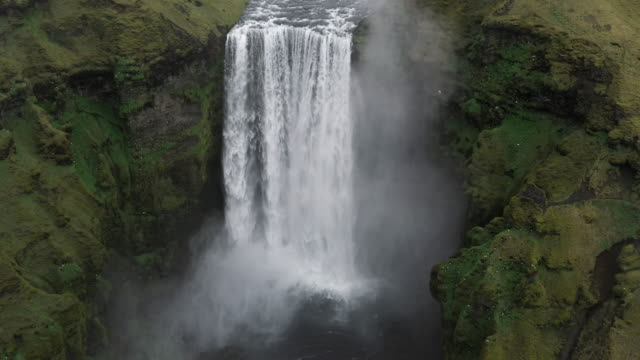 drone view tilting down and flying towards skógafoss waterfall, iceland - contrasts stock videos & royalty-free footage