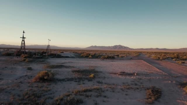 a drone views a broken windmill and sunset in rachel nevada - nevada stock-videos und b-roll-filmmaterial