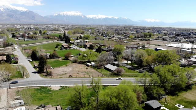 a drone views lehi city with snow capped mountains in the background in lehi utah - lehi stock videos & royalty-free footage