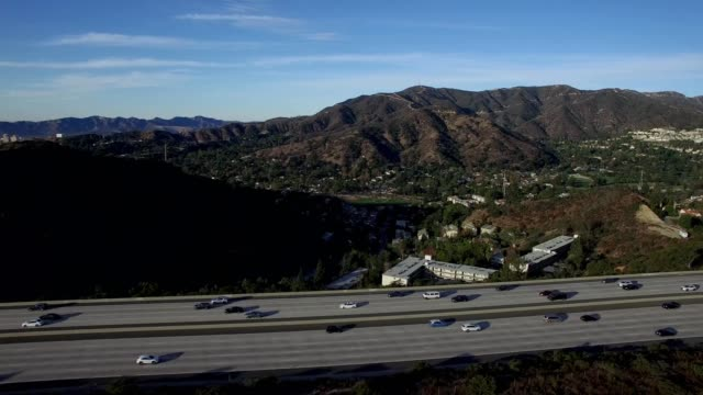 a drone views mountains and a freeway in los angeles california - dronebase stock videos and b-roll footage
