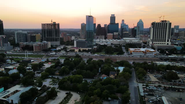 drone views of a busy austin , texas at golden hour sunset above downtown skyline and i-35 highway - high street stock videos & royalty-free footage