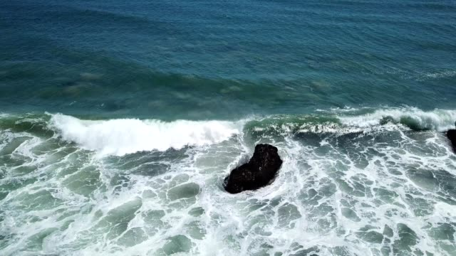 a drone watches waves crash on a rock at a beach in malibu california - malibu stock videos & royalty-free footage