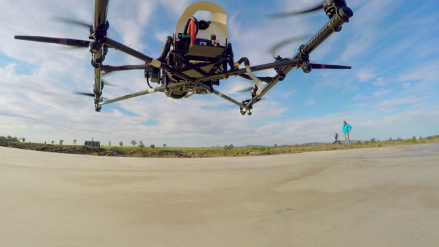 A drone with a camera and several propellers takes off and flies against a cloudy blue sky