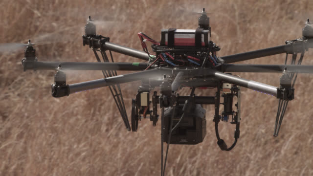 Drone with camera flies over grassland, India