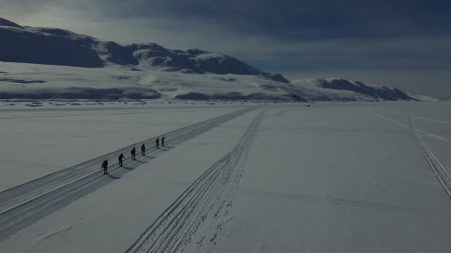 dronefootage of group of skiiers - seen from behing - ice sheet stock videos and b-roll footage