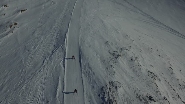 Dronefootage of skiiers going down hill
