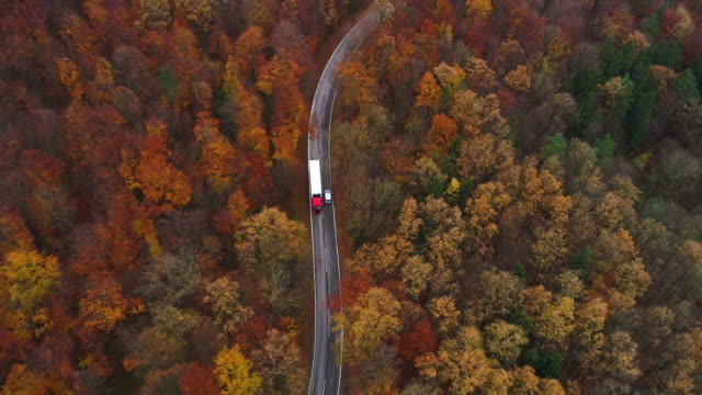 Drones: an aerial road trip - following truck on country road aerial view 4K
