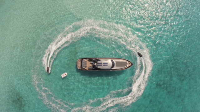 drones birds eye view of jet skis circling luxury yacht - 豊か点の映像素材/bロール