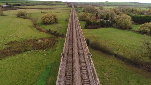 drones eye view along the harringworth railway viaduct. - railway bridge stock videos & royalty-free footage