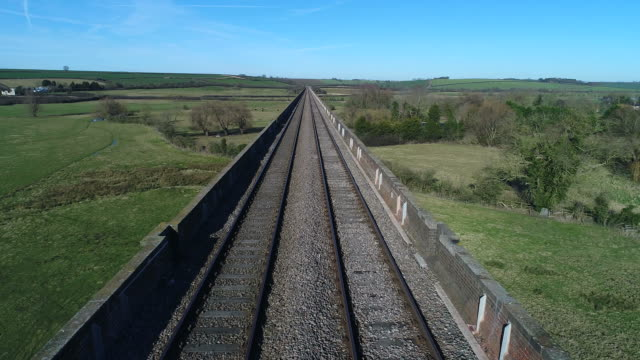 drones eye view along the harringworth railway viaduct, - rail transportation stock videos & royalty-free footage
