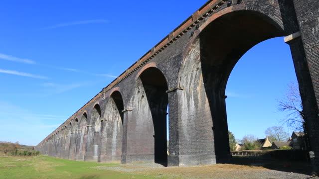 drones eye view along the harringworth railway viaduct, - arch bridge stock videos and b-roll footage
