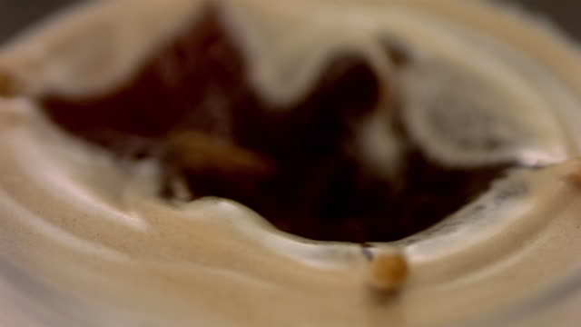 vídeos de stock e filmes b-roll de slo mo ecu drop falling into coffee - castanho