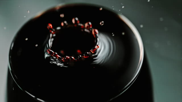 SLO MO Drop of a red wine dripping into a glass