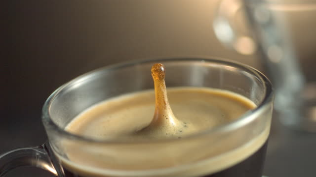 vídeos de stock, filmes e b-roll de a drop of coffee splashes into cream and coffee in a glass cup. - xícara de café