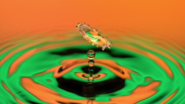 slo mo ld drop of water falling onto a calm water surface lit with orange and green light - sine wave stock videos & royalty-free footage