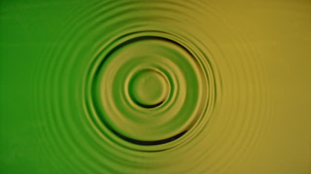 slo mo ld a droplet creating a splash and concentric ripples when hitting the green and yellow coloured  surface - rippled stock videos & royalty-free footage