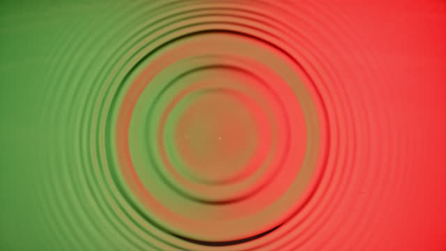 slo mo ld a droplet creating a splash and concentric ripples when hitting the green and red coloured  surface - concentric stock videos & royalty-free footage