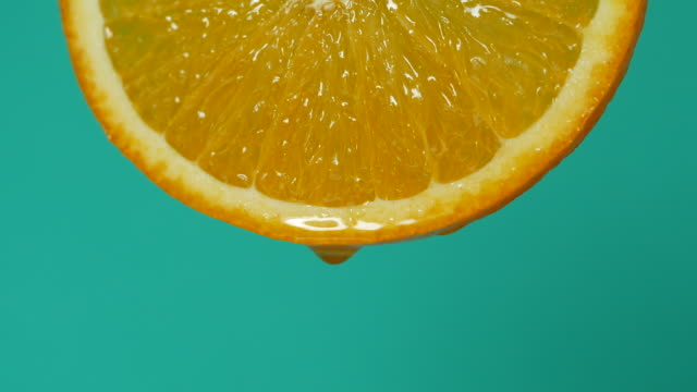 droplet of honey falling from orange fruit slice - coloured background stock videos & royalty-free footage