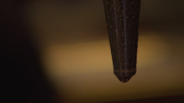 A droplet slowly forms at the tip of a beer tap, UK.