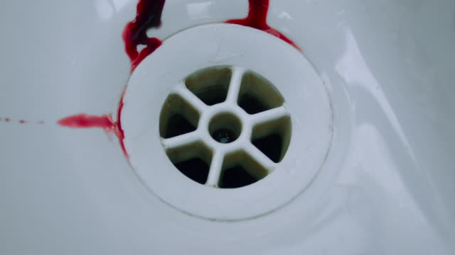 Droplets of blood stream into a sink