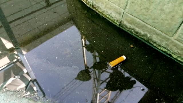 排水溝にタバコの吸殻を落とした - 廃棄物処理点の映像素材/bロール
