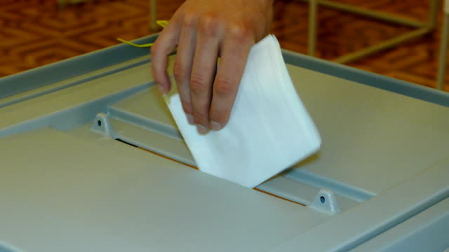 vídeos de stock e filmes b-roll de dropping an elected ballot into the ballot box for voting - eleições