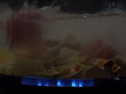 vídeos de stock e filmes b-roll de dropping assorted varieties of pasta into a pot of water - alimento básico