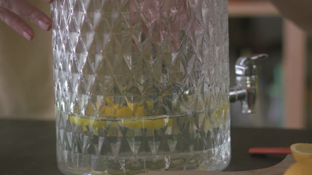dropping lemons into a glass jar with lemonade - pitcher jug stock videos & royalty-free footage