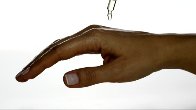 Dropping serum on woman's hand from a glass Pipette
