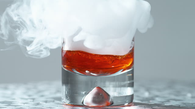 dropping smoky dry ice in a glass with liquor / slow motion - alkoholisches getränk stock-videos und b-roll-filmmaterial