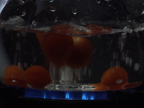 dropping tomatoes into a pot of boiling water over a gas flame - boiling stock videos & royalty-free footage