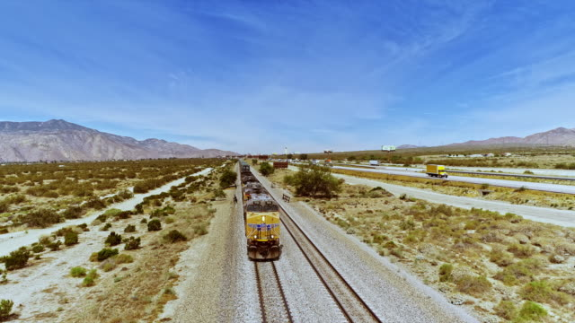 ws drops down from high angle view of freight train hauling cargo alongside busy california interstate 10 traveling south towards indio - interstate 10 stock videos & royalty-free footage