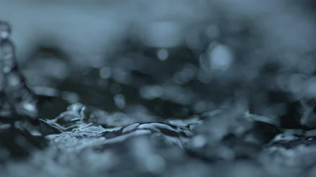 vídeos de stock, filmes e b-roll de drops fall and cause splashes as surface tension is overcome. - tensão de superfície