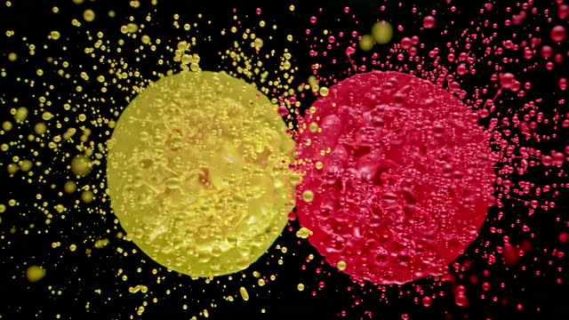 slo mo ld drops flying into the air from a yellow and red colour blotches - two objects stock videos & royalty-free footage