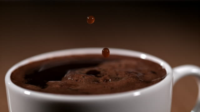 slo mo drops of a coffee falling into a cup - pouring stock videos & royalty-free footage