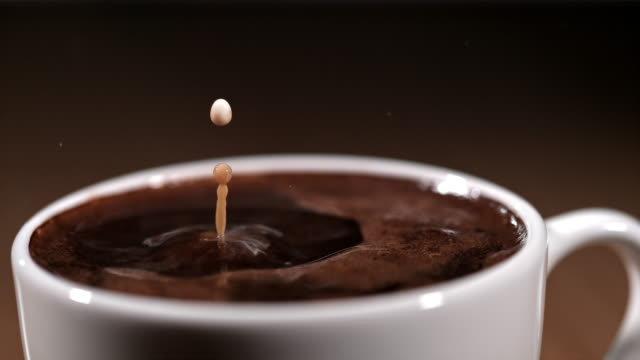 slo mo drops of a milk falling into a cup of coffee - pouring milk stock videos & royalty-free footage