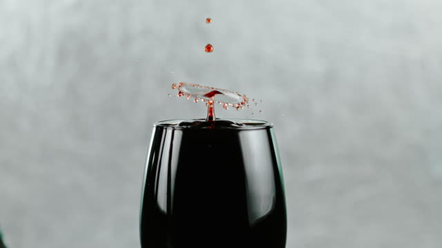 SLO MO Drops of a red wine dripping into a glass