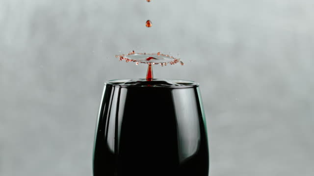 SLO MO Drops of a red wine splashing into a glass