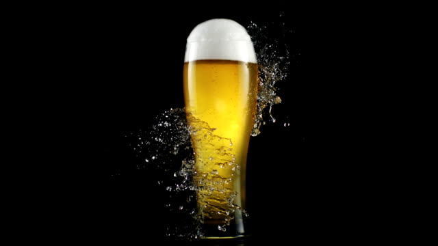vídeos de stock e filmes b-roll de drops of water crashing on a glass full of beer. freshness metaphor - beer alcohol