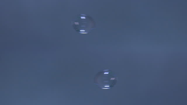 drops of water fall towards each other. - blue background stock videos & royalty-free footage