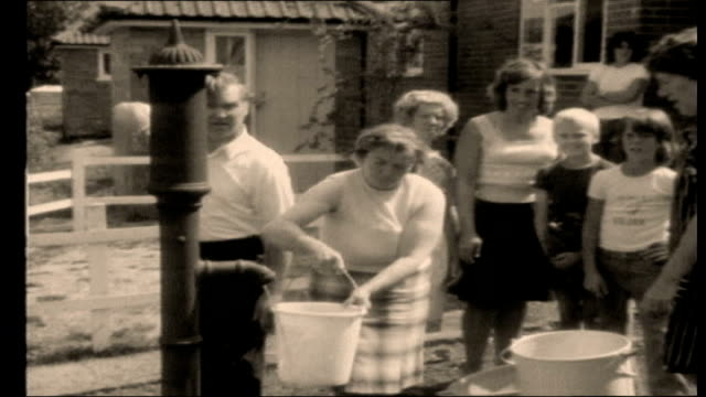 vídeos de stock, filmes e b-roll de drought warning for southern england graphicised seq 1976 drought people using standpipe in street/ dried and cracked bed of reservoir - 1976